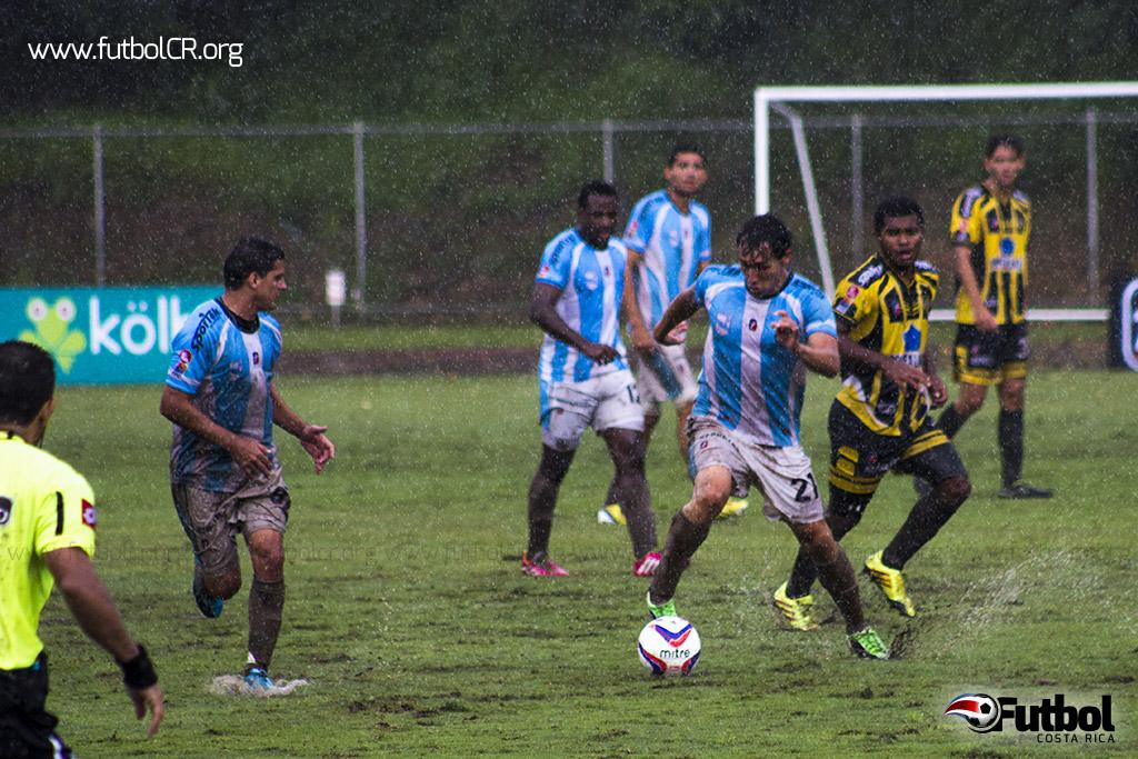 Victor Coto domina el balón con la marca de un defensor lechero, durante el lluvioso segundo tiempo del juego del medio día del  domingo.